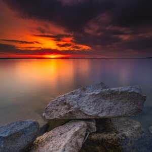 It's an image of a sunrise near the water and rocks nearby.